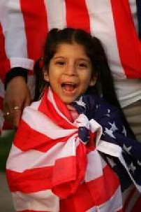 a cute girl (approximately 5 years old) with the American flag draped around her shoulders