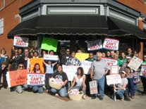 group of people with signs calling for health care reform posing for the camera in front of a store