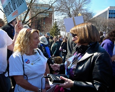 photo of Melanie Collins being interviewed by a reporter at a rally